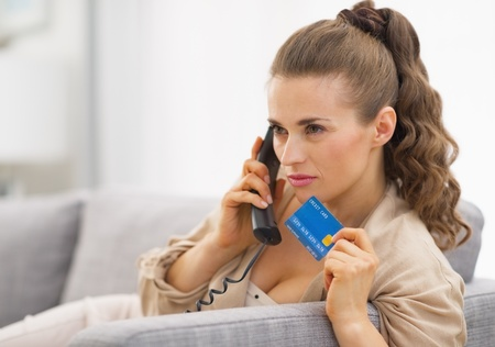 disquieted: Concerned young woman with credit card talking phone