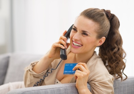 Happy young woman with credit card talking phone Stock Photo - 21792491