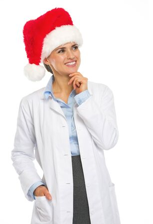 heal new year: Happy doctor woman in santa hat looking on copy space