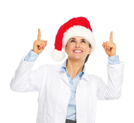 heal new year: Smiling doctor woman in santa hat pointing up on copy space