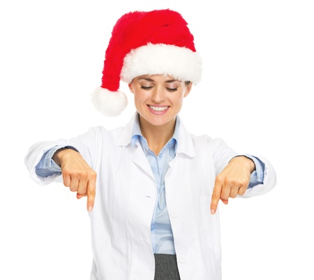 heal new year: Smiling doctor woman in santa hat pointing down on copy space Stock Photo