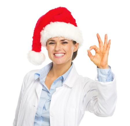heal new year: Happy doctor woman in santa hat showing ok gesture