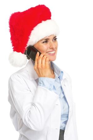 heal new year: Happy doctor woman in santa hat talking mobile phone