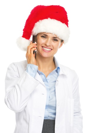 Smiling doctor woman in santa hat talking cell phone photo