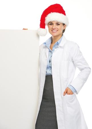 heal new year: Happy doctor woman in santa hat showing blank billboard Stock Photo