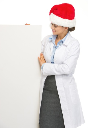 heal new year: Happy doctor woman in santa hat looking on blank billboard Stock Photo