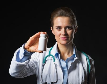 Doctor woman showing medicine bottle on black background photo