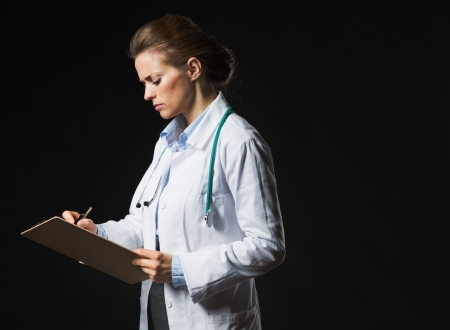 Serious doctor woman writing in clipboard isolated on black photo