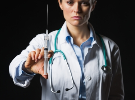 Closeup on syringe in hand of doctor woman isolated on black photo