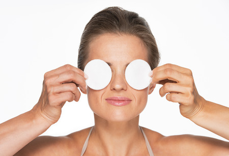 Woman holding cotton pads in front of eyes