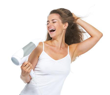 Smiling young woman singing while blow-dry Stock Photo - 22334538