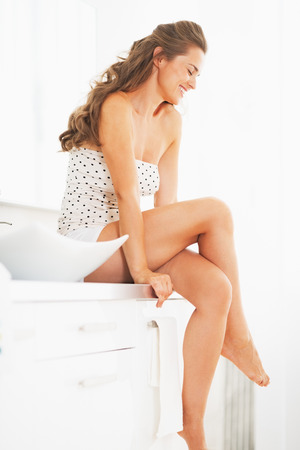 underclothes: Portrait of happy young woman sitting in bathroom