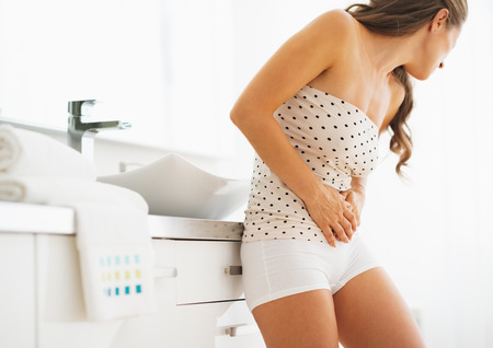 bulimia: Woman having stomachache in bathroom Stock Photo