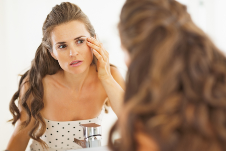 disquieted: Concerned woman checking facial skin condition in bathroom