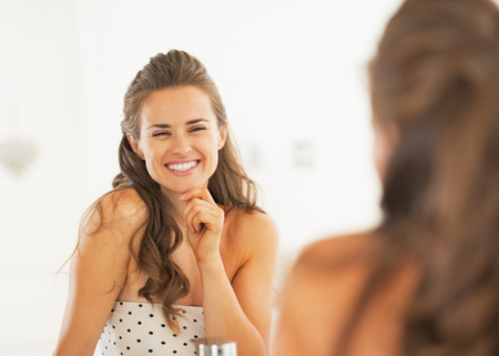 Smiling woman looking in mirror in bathroom photo