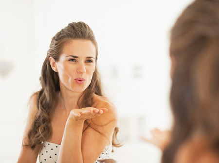 bathroom mirror: Young woman blowing air kiss in mirror