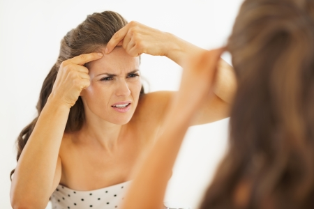 pimples: Concerned young woman squeezing acne in bathroom Stock Photo