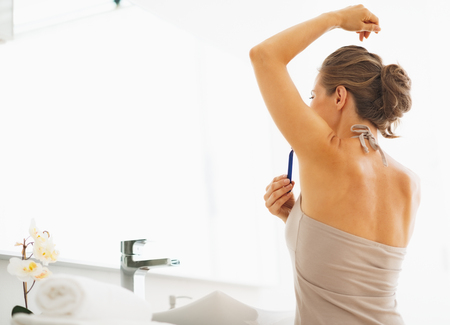 axilla: Woman shaving armpit in bathroom
