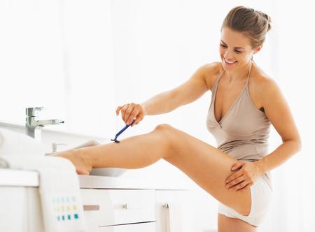 aseo personal: Mujer que afeita las piernas en el baño