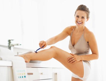 hygienics: Smiling woman shaving legs in bathroom
