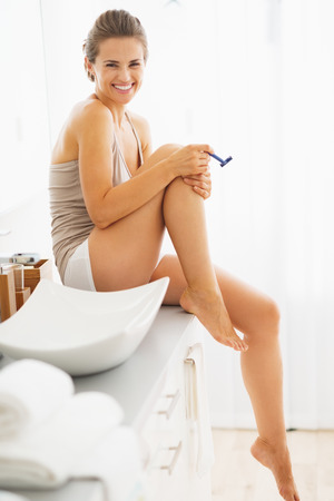 shave: Happy woman shaving legs in bathroom
