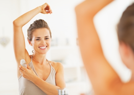 axilla: Smiling young woman applying roller deodorant on underarm in bathroom Stock Photo