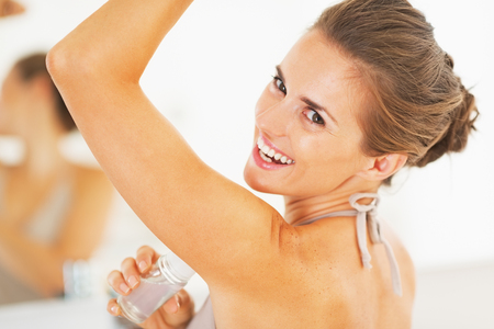 perspiration: Smiling young woman applying roller deodorant on underarm in bathroom Stock Photo