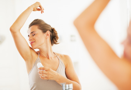 axilla: Woman enjoying freshness after applying roller deodorant on underarm Stock Photo