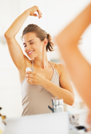 underarm: Happy woman enjoying freshness after applying roller deodorant on underarm