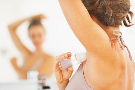 axilla: Closeup on woman applying roller deodorant on underarm