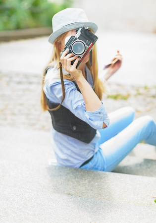 youthfulness: Hipster girl making photo with retro camera while sitting on stairs