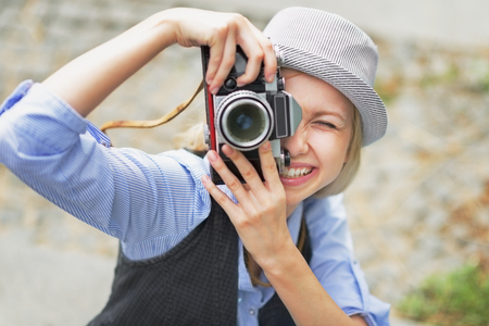 youthfulness: Smiling hipster girl making photo with retro camera