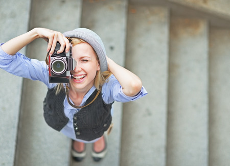 Happy hipster girl making photo with retro camera on city street