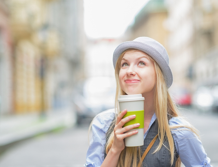 Thoughtful hipster girl with cup of hot beverage on city street photo