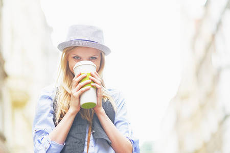 Hipster girl drinking hot beverage on city street Stock Photo