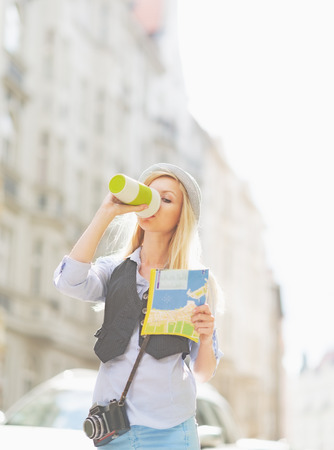 Tourist girl with map drinking hot beverage on city street photo