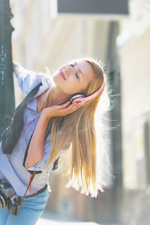 youthfulness: Happy hipster girl listening music on city street