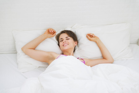 catnap: Happy young woman stretching in bed after sleep