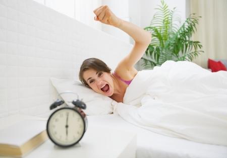 awakened: Angry young woman wants to break awakened her alarm clock Stock Photo