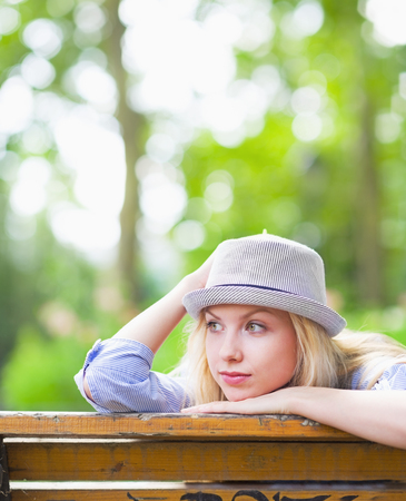 Thoughtful hipster girl sitting on bench in the park and looking on copy space photo