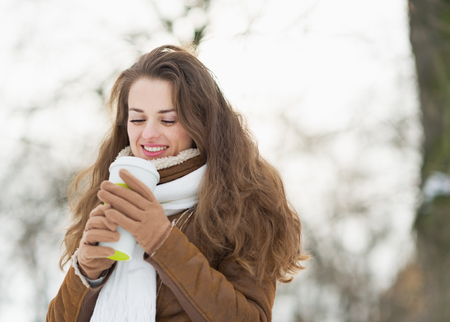 Happy young woman holding cup of hot beverage in winter park photo