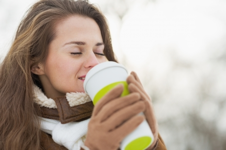 Happy young woman holding cup of hot beverage in winter outdoors photo