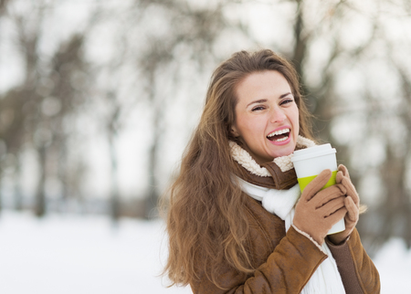Smiling young woman with cup of hot beverage in winter park photo