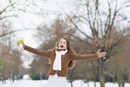 Happy young woman with cup of hot beverage in winter outdoors rejoicing photo