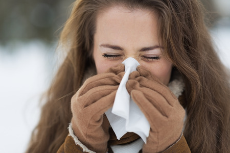 Young woman blowing nose in winter outdoors Stock Photo - 22518612
