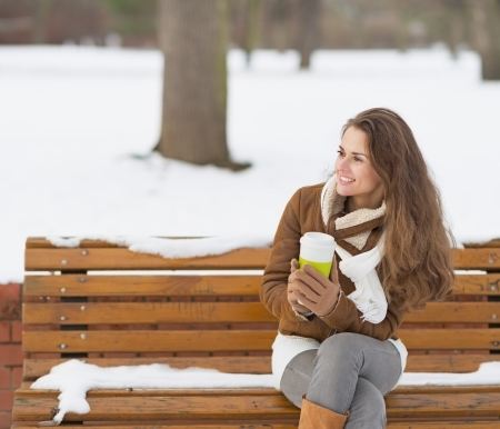 Happy young woman with cup of hot beverage sitting on bench and looking on copy space photo