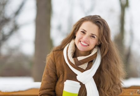 Happy young woman with cup of hot beverage sitting on bench in winter outdoors photo