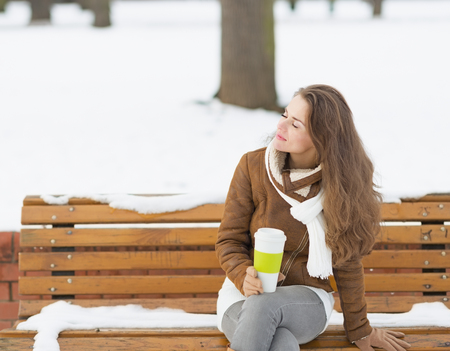 Happy young woman with cup of hot beverage enjoying winter photo