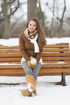 Happy young woman with cup of hot beverage sitting on bench in winter park photo