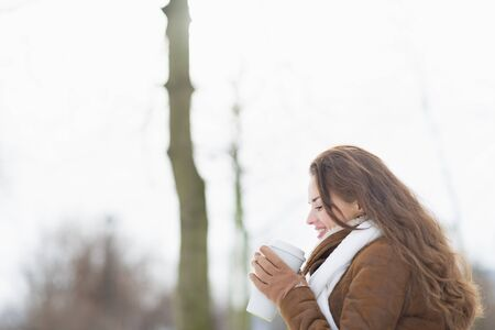 Happy young woman enjoying cup of hot beverage in winter outdoors photo